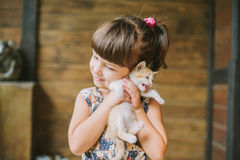 Cheerful little girl holding a frightened cat in hands Royalty Free Stock Images
