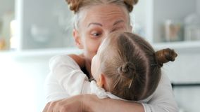 Cheerful little girl hugs her mother on the kitchen