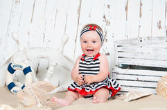 Cheerful Little Girl In A Marine Style Sits On The Sand Royalty Free Stock Image