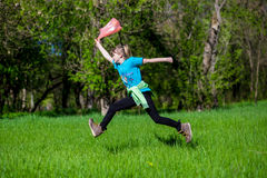 Cheerful little girl jump on the grass with a package Royalty Free Stock Photos