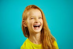 Cheerful little girl laughs a sincere expression of feelings, portrait of happy child on blue background. royalty free stock photos