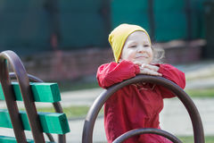 Cheerful little girl leaning street bench and putting her head on hands Stock Photos