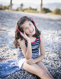 Cheerful little girl listening to music. On headphones Stock Photos