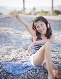 Cheerful little girl listening to music. On headphones Royalty Free Stock Images