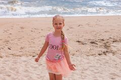 Cheerful little girl with long blonde hair in pink tulle skirt walking empty sea beach alone. Beautiful little princess