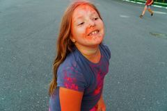 Cheerful little girl with long hair covered pink and purple dry paint Holi royalty free stock images