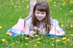 Cheerful little girl lying on a beautiful coverlet in the grass. Stock Images