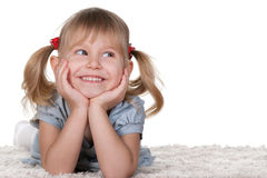 Cheerful little girl lying on the carpet Stock Images