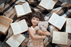 Cheerful little girl lying on floor with lot of books; stock photos