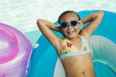 Cheerful Little Girl Lying On Inflatable Raft In Pool. Portrait of a cheerful little girl lying on inflatable raft in swimming pool Royalty Free Stock Photography