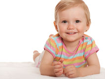 Cheerful little girl lying on the white Stock Photos