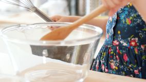 Cheerful little girl mixed the ingredients for baking cookies. Close up stock video footage