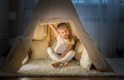 Little girl in teepee tent in room. Cheerful little girl in pajamas sitting in cozy teepee tent in her room royalty free stock photography