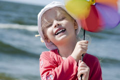 Cheerful little girl with pinwheel III Stock Photos