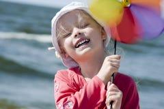 Cheerful little girl with pinwheel III Stock Photos