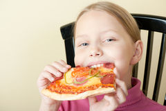 Cheerful little girl with pizza Stock Photos
