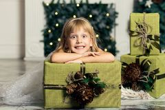 Cheerful little girl is playing with gifts on the background of a Christmas tree Royalty Free Stock Photography
