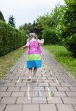 Cute cheerful little girl playing hopscotch on playground. Turning away from the camera royalty free stock photo