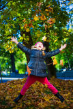 Cheerful little girl playing with maple leaves in park Royalty Free Stock Photo