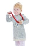 Cheerful little girl put on her big red beads Royalty Free Stock Photography