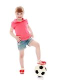 Cheerful little girl put her foot on a soccer ball Stock Images