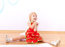 Cheerful little girl in red apron Stock Photo