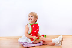 Cheerful little girl in red apron Royalty Free Stock Photography