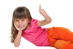 Cheerful little girl rests. Laughing little girl with her thumb up is lying on the white background royalty free stock photo