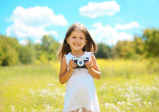Cheerful little girl with retro camera. In summer sunny day Royalty Free Stock Images