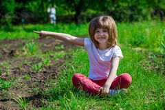 Cheerful little girl sit in green grass and point to the something. In summer day stock photos