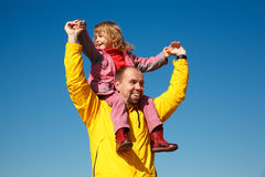 Cheerful little girl sits on shoulders at man Royalty Free Stock Photo