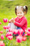 Cheerful little girl sitting in grass looking at tulips Stock Photos