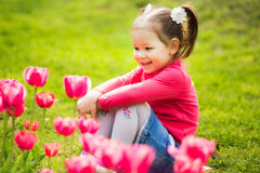 Cheerful little girl sitting in grass looking at tulips Stock Photo