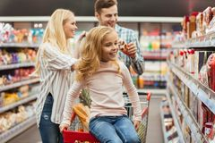 Cheerful little girl sitting on a shopping cart. And choosing sweets with her parents at the supermarket Royalty Free Stock Photography