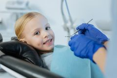 Cheerful little girl smiling while having oral cavity checkup. Brave little patient. Cute little girl lying in a dentist chair and smiling at the camera while Royalty Free Stock Images