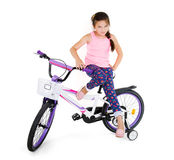 Cheerful little girl on a sports bike on a white background Royalty Free Stock Images