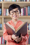 Cheerful little girl studying with book in library Royalty Free Stock Photos