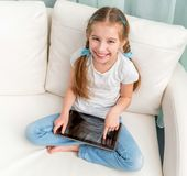 Cheerful little girl with tablet on her legs looking at camera. Cheerful little girl on sofa with tablet on her legs looking at camera Royalty Free Stock Photo