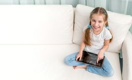 Cheerful little girl with tablet on her legs looking at camera. Cheerful little girl on sofa with tablet on her legs looking at camera Royalty Free Stock Photography