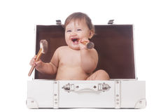 Cheerful little girl. With two make-up brushes sitting in a suitcase on isolated white stock image