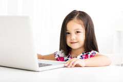 Cheerful little girl using the laptop Royalty Free Stock Photo