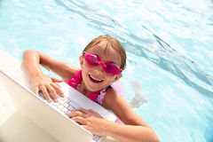 Cheerful little girl using laptop in swimming pool stock photography