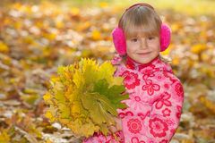 Cheerful little girl with yellow leaves Royalty Free Stock Image