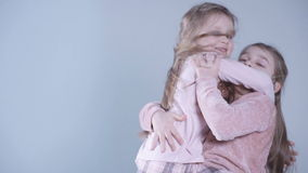Cheerful little girls posing over white background. Two lovely little girls playing in studio. Younger sister jumping straight to an older's arms in slow motion stock video footage