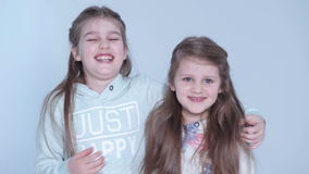 Cheerful little girls standing over white background and smiling. stock video