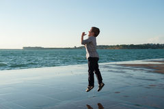 Cheerful little kid jumping on the background of sea port. Cheerful little boy jumping on the background of sea port at sunset stock photos