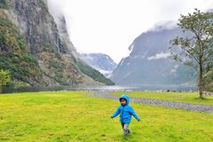 Cheerful little kid running and playing in Gudvangen village`s harbour, a popular tourist destination located atNærøyfjord. Cheerful little kid running and royalty free stock photography