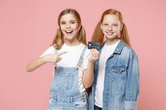 Free Cheerful Little Kids Girls 12-13 Years Old In White T-shirt, Denim Clothes Isolated On Pastel Pink Background. Childhood Stock Images - 192640004