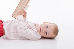 Cheerful little male child is learning letters. Pretty boy is lying on flooring and reading a book. He looking at the camera with interest and smiling. Isolated Royalty Free Stock Photos