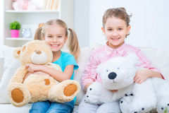 Cheerful little sisters sitting on the sofa Royalty Free Stock Photos